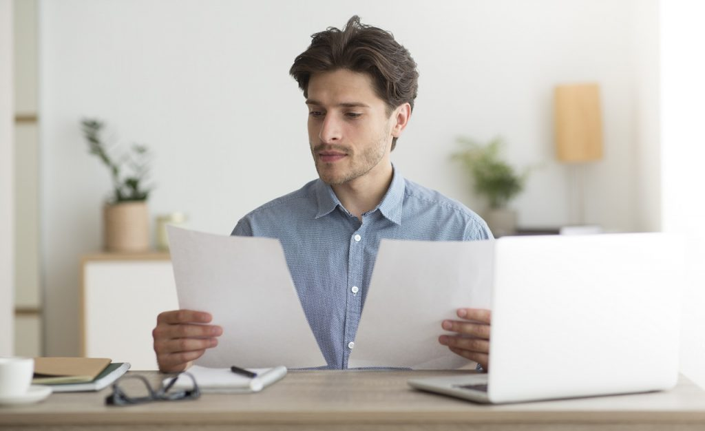 Business Man Working With Papers Sitting At Laptop In Office