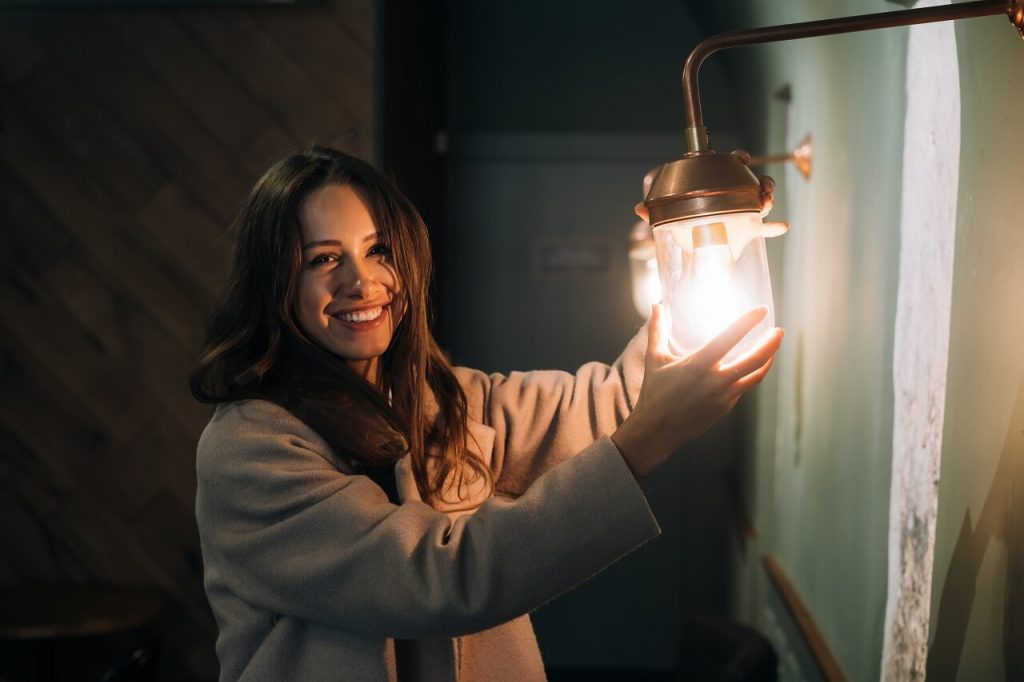young woman holding a bigger light bulb